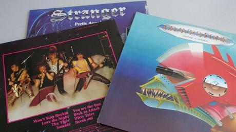 Bei Heavy Metal musste es wild und gefährlich zugehen, wie die Albumcover von Gravestone und Stranger zeigen. Heute sehen die Herren von Gravestone trotz der Lederjacken deutlich gesetzter aus.
