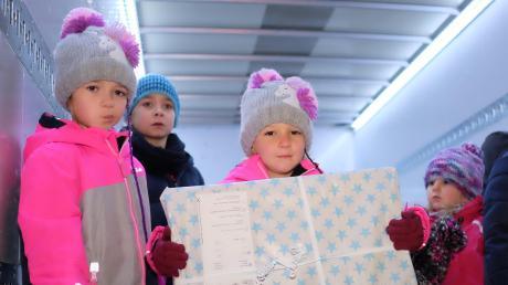 Die vierjährige Marie (Mitte) hat ein großes Geschenk für den Nikolauskonvoi in Pfaffenhofen gepackt. Ein Lkw bringt ihr Paket gemeinsam mit Dutzenden anderen nach Rumänien, wo sie an arme Kinder verteilt werden.