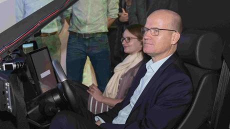 Klaus Dietmayer (links) in einem autonomfahrenden Versuchsauto: Rechts: Ralph Brinkhaus und Ronja Kemmer im Ulmer Fahrsimulator.