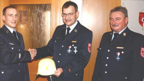 Den Kommandantenhelm gibt Georg Thalhofer (Mitte) unter den Augen des Vorsitzenden Dieter Müller (rechts) an seinen Nachfolger Martin Müller als symbolische Geste weiter.