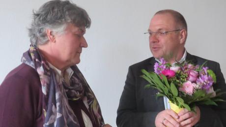 Pfarrer Tobias Praetorius überreicht der Vereinsvorsitzenden Elisabeth Eisenmann mit Blumen.