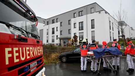 Feuerwehrleute vor dem Mehrfamilienhaus in Ulm, in dem es einen Wohnungsbrand gab.