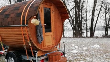 Das Saunafass ist nicht auf einen Stromanschluss angewiesen, weil es mit Holz beheizt wird und das Licht batteriebetrieben ist. Hier steht es an einem See.