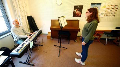 So sieht der Gesangsunterricht mit Lehrer Jens Blockwitz am Keyboard und Schülerin Marie Sophie Kölle in der Neu-Ulmer Musikschule aus. Seit Montag darf im großen Raum wieder geprobt werden. Wer entdeckt das kleine Accessoire am Notenständer?