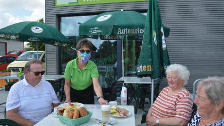 """Geschäftsführerin Sabine Penski bringt kleine Speisen und Kaffee in den außen liegenden Gastrobereich. Das """"Café Witzig"""" bietet wechselnde Gerichte – und auch ein Feierabendbier."""