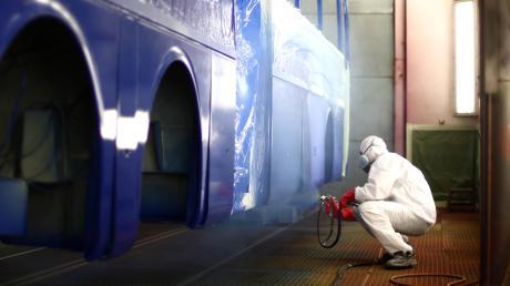 Ein Evobus-Mitarbeiter lackiert im Neu-Ulmer Werk einen Reisebus.