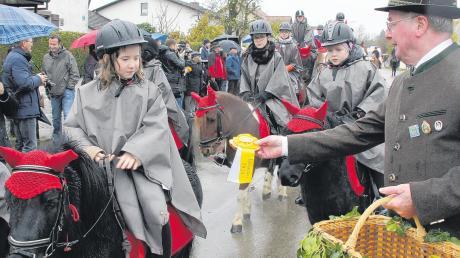 Am Ende des Leonhardiritts in Laisacker verteilten Mitglieder des Schützenvereins an die Teilnehmer Erinnerungsrosetten.