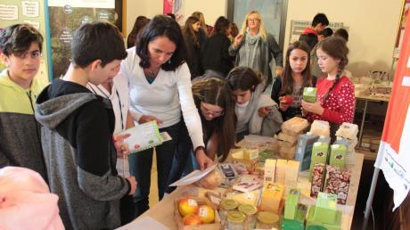 """Die Schüler der Klasse 7c der Mittelschule Neuburg gehen im """"Klimaladen"""" fiktiv einkaufen. Für nachhaltige Lebensmittel erhalten sie einen grünen Smiley und einen roten für Lebensmittel, die die Umwelt belasten. Durch die interaktive Ausstellung lernen die Kinder spielerisch, wie sie im Kleinen doch viel bewirken können."""