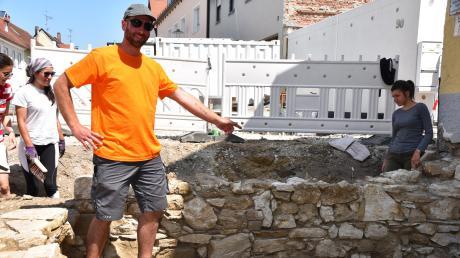 Der stellvertretende Grabungsleiter Julian Schwiatkowski zeigt auf Fundamente eines Hauses.