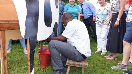 Es ist gar nicht so einfach, Kuh Alma ein bisschen Milch bzw. Wasser zu entlocken. Pfarrer Paul Igbo schlug sich beim Melkwettbewerb allerdings gar nicht so schlecht.