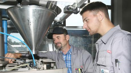 Werkstattleiter Norbert Pelger (li.) erklärt Auszubildenden Lukas Oggermüller die richtigen Einstellungen an einer Abfüllanlage.