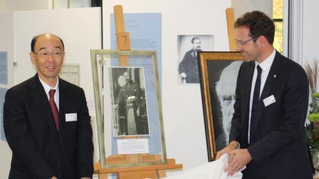 Prof. Dr. Chisato Mori (links) und Landrat Peter von der Grün enthüllen ein Bildnis von Mori Ogai, das im Beruflichen Schulzentrum Max von Pettenkofer an den japanischen Schüler des berühmten Hygienikers erinnert.
