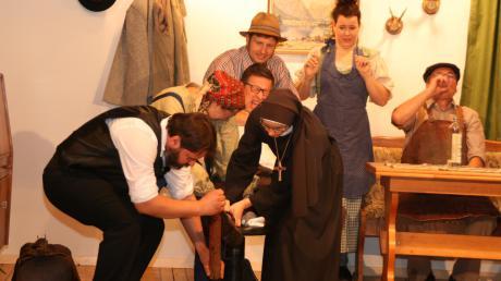 Gemeinsam versuchen die Akteure in dieser Szene, dem Bauer Dugg Bertl (Fred Braumandl) den rostigen Nagel aus dem Fuß zu ziehen.