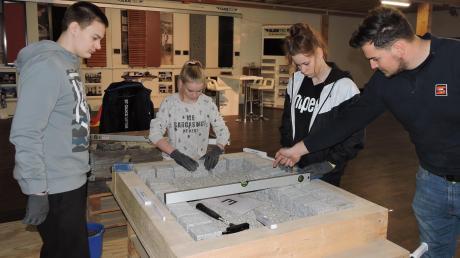 """""""Alles im Wasser"""" zeigt die Wasserwaage an, wenn alles passt. Bauingenieur Johannes Bauer (rechts) führte den Mädchen und Burschen vor, wie es im Straßenbau richtig gemacht wird."""