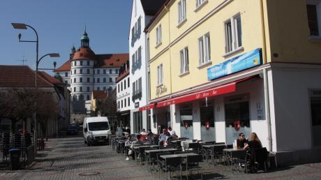 Öffentliches Leben in Zeiten von Corona auf dem Neuburger Schrannenplatz. Solange keine Ausgangssperre verhängt ist, ist es noch möglich, zu den verkürzten Öffnungszeiten in Cafés und Lokalen dem schönen Wetter zu frönen.
