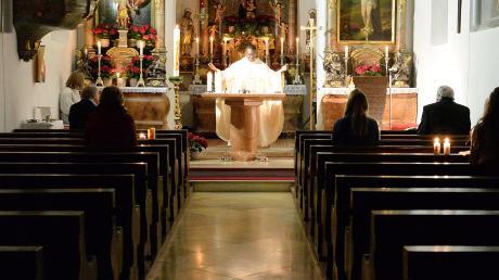 In der noch dunklen Bittenbrunner Kirche feiert Kaplan Jerome Muyanga mit ganz wenigen Besuchern die Osternacht.