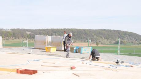 In luftiger Höhe mit Blick auf den Weinberg arbeiten die Zimmerer der Firma Horwart aus Tannhausen am Dach der neuen Rennertshofener Grundschule und bringen gerade die Sichtschalung ein.