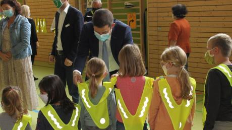 Weicherings Bürgermeister Thomas Mack verteilt Westen an die Schüler.