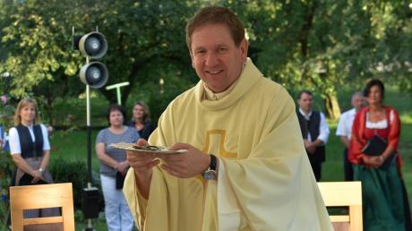 Pfarrer Konrad Willi hält einen symbolischen Kirchenschlüssel in der Hand, den er von Domkapitular Josef Funk überreicht bekommen hatte.