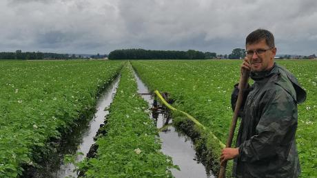 Bis zu den Waden steht Alexander Edler in seinem Kartoffelacker im Wasser. In den Fahrfurchen zeigt sich die Überschwemmung besonders gut, aber auch in den Kartoffelreihen steht das Wasser.
