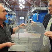 Erich Reng (links) von den Stadtwerken zeigt Oberbürgermeister Bernhard Gmehling eines der Gitternetze aus dem Luftschaft beim Wasserwerk in Sehensand. Weil sie nicht feinmaschig genug waren, konnten sich Mücken darin verfangen. Die Fäkalienbakterien waren vor vier Jahren der Grund für die Belastung des Trinkwassers.