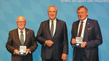 """Als """"Dankeschön des Freistaates"""" überreichte Innenminister Joachim Herrmann Verdienstmedaillen an Alois Rauscher (l.) und Bernhard Gmehling (r)."""