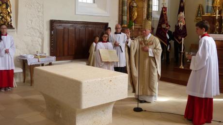 Weihbischof Dr. Dr. Anton Losinger segnet den neuen Altar der Deininger Martinskirche mit Weihwasser.