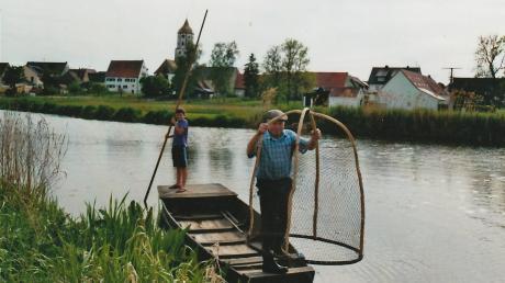 Otto Bühler, Senior der heutigen Fischer-Familie mit Enkel, zeigt die frühere Fangtechnik mit dem Fisch-Storz. Sie wurde 1960 letztmals zum Waller- und Karpfenfang angewendet. Rechts im Hintergrund die Bühler-Hofstätte.