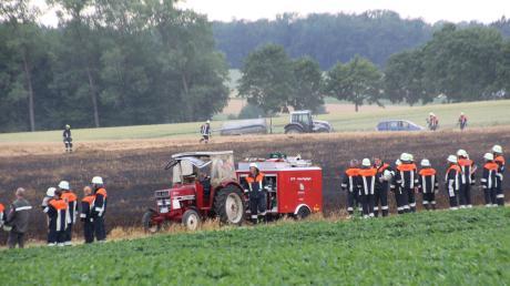 Einsatzkräfte und Helfer blicken auf das verbrannte Feld.