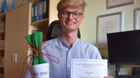 Michael Burger hat am Albrecht-Ernst-Gymnasium das Abitur abgelegt. Mit 894 von 900 möglichen Punkten. In seinem Zimmer präsentiert er das Zeugnis und das Abschlussgeschenk des Elternbeirats an alle Schüler.