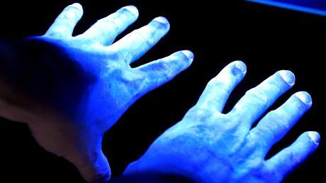 Das UV-Licht macht Verunreinigungen auf den Händen sichtbar, in diesem Fall Bakterien. In der Region gibt es Firmen, bei denen sich in diesen Tagen die Hygienevorschriften verschärfen. Hintergrund ist das Corona-Virus.