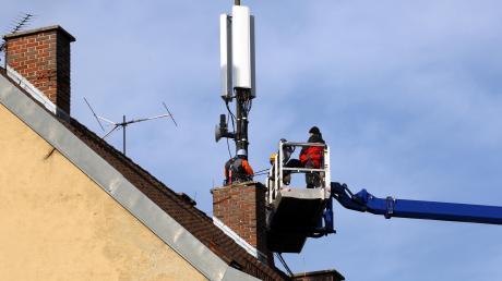 Ein Mobilfunkmast wird auf einem Gebäude montiert. Einigen sich Kommunen nicht mit der Telekom, kontaktiert das Unternehmen in manchen Fällen Privatleute, um den wirtschaftlichsten Standort für die Mobilfunkversorgung zu finden.