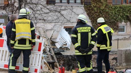 Einsatzleiter und Helfer der Feuerwehr begutachten die Baugrube, in der es am Montagnachmittag zu einer Gasexplosion gekommen ist.