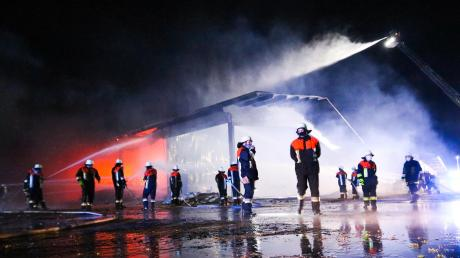 Feuerwehrleute versuchen sowohl am Boden als auch aus der Luft das Feuer in einer Maschinenhalle in Munningen zu löschen. Nach ersten Erkenntnissen geht die Polizei von einem Millionenschaden aus. Das Grundstück ist weiträumig abgesperrt, denn es herrscht Einsturzgefahr.