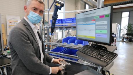 """SPN-Geschäftsführer Rainer Hertle steht an einem Systemarbeitsplatz. Im Forschungsprojekt ging es unter anderem darum, Arbeitsabläufe digitaler und effizienter zu gestalten. Der Forschungsverbund heißt SynDiQuAss und steht für """"Synchronisierung von Digitalisierung, Qualitätssicherung und Assistenzsystemen an Arbeitsplätzen mit geringem Automatisierungsgrad""""."""
