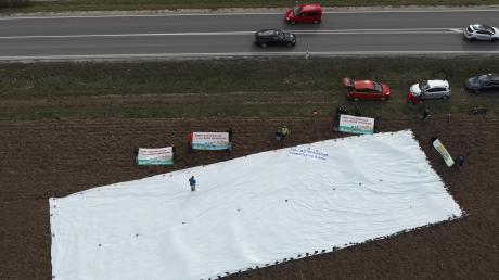 """Um einen Eindruck zu bekommen, wie viel Fläche bei einer Umgehung Möttingens verbraucht werden könnte, hat die Initiative """"B25 Mittendrin"""" eine weiße Plane auf ein Feld gelegt. Sie ist zwölf Meter breit, eine Umfahrung hätte sogar eine Breite von mehr als 15 Metern, sagt ein Sprecher der Ortsgruppe Bund Naturschutz Nördlingen."""