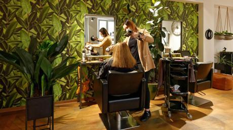 Im Friseursalon Element-Haar föhnt Inhaberin Isabella Baur die Haare einer Kundin. Die Friseurin würde lieber auf die Ehrlichkeit und Vernunft ihrer Kunden vertrauen, als sich ein negatives Testergebnis oder eine Vollimpfung bestätigen zu lassen.