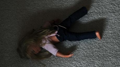 Eine Puppe liegt in einem Kinderzimmer auf dem Teppich (Symbolbild): Das BKA sucht nach einem Mann, der ein Baby mehrfach schwer sexuell missbraucht haben soll. Nach Polizeiangaben sind bislang rund 100 Hinweise eingegangen.