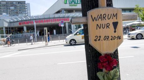 Ein Holzkreuz mit der Aufschrift «Warum nur!» hängt vor dem OEZ. Foto: Peter Kneffel/Archiv