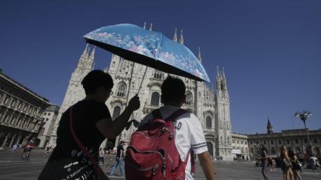 Touristen gehen in Mailand bei großer Hitze unter einem Sonnenschirm am Dom vorbei. Foto: Luca Bruno
