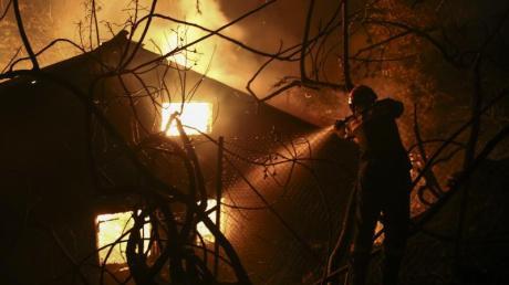 Ein Feuerwehrmann versucht ein brennendes Haus zu löschen. Foto: Yorgos Karahalis