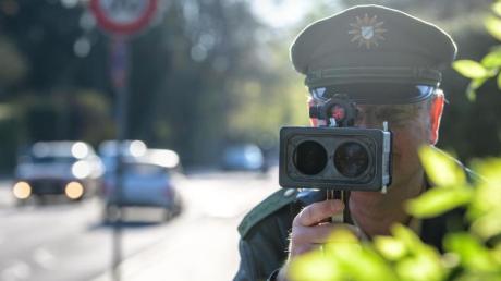 An einer Grundschule in München misst ein Polizist mit einer Laserpistole die Geschwindigkeit vorbeifahrender Fahrzeuge. Foto: Matthias Balk
