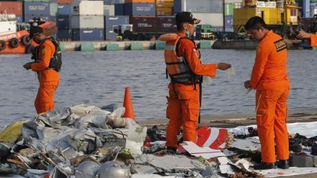 Mitarbeiter der Indonesischen Such- und Rettungsbehörde inspizieren Trümmerteile.