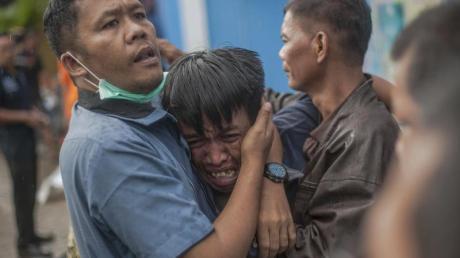 Ein Mann reagiert, nachdem er einen Verwandten als Opfer der Todeswelle identifiziert hat.