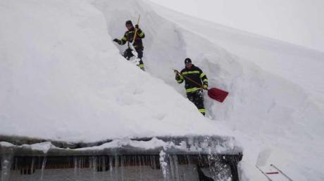 Einsatzkräfte räumen Schnee vom Dach eines Hauses im oberösterreichischen Kirchdorf an der Krems.
