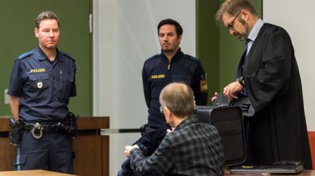 Der Angeklagte (M) sitzt in einem Saal des Landgerichts München II.