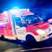 Ein Rettungswagen der Feuerwehr mit Blaulicht bei einemEinsatz. Foto: Marcel Kusch/Archiv