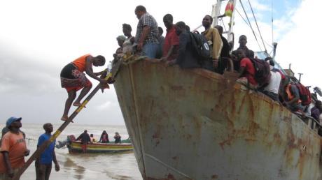 Ein Boot mit etwa 100 Menschen, die aus der überfluteten Region Buzi gerettet wurden, legt an einem Strand an. Foto: Kate Bartlett