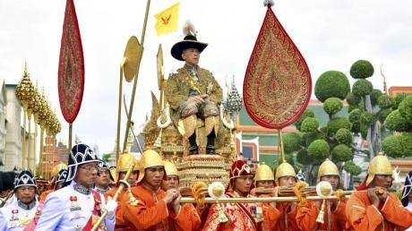 König Maha Vajiralongkornwird auf einer Sänfte durch die Straßen getragen. Er ist der zehnte König seit Beginn der Chakri-Dynastie 1782 und trägt auch den Namen Rama X.