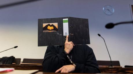 Der Angeklagte Bernhard H. versteckt sein Gesicht hinter einem Aktenordner. Auf dem klebt ein ziemlich merkwürdiges Foto.
